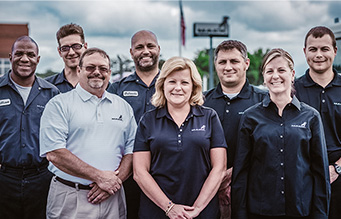 Mack Trucks employees standing with Mack Trucks Dealer